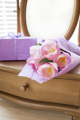 Pink tulips in violet paper, gift and mirror, backlight background