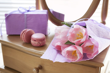 Pink tulips in violet paper, two pink macaroons, gift and mirror, backlight background