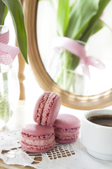 Three pink macaroons and cup of coffee, pink tulips and mirror, backlight background