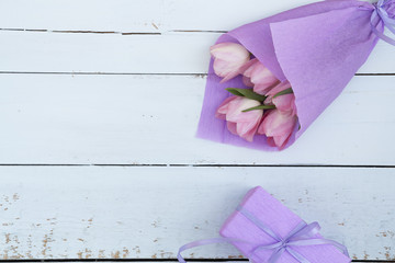 Beautiful bouquet of pink tulips in violet paper and gift on light wooden background