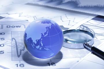 グローバルファイナンス/ガラス製の地球とファイナンシャルチャートとルーペ/アジア大陸
