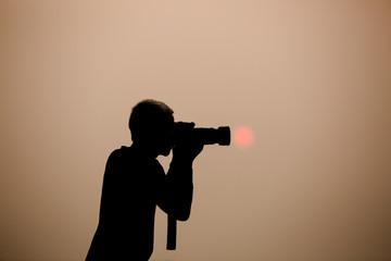 silhouette photographer at sunrise