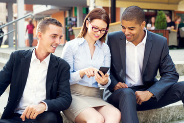 Group of business people sitting at stairs in front of their office and looking at smart phone.