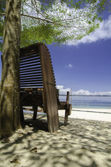 cropped image of wooden chair facing the beach at sunny day.cloudy blue sky with clear blue sea water background. image taken at Kapas Island, Malaysia.