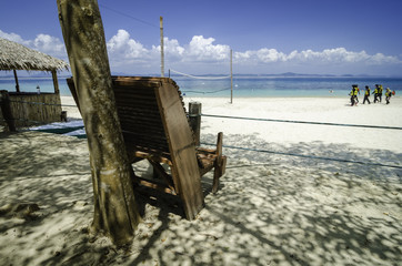 lonely wooden beach chair under a tree facing clear blue sea water and white sandy beach. cloudy blue sky.group of tourists with life jacket ready for island hopping.