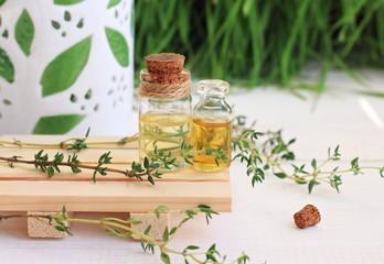 Essential thyme oil in bottles. Aroma lamp, fresh green herbs.