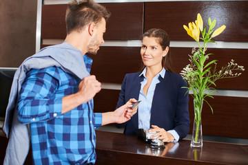 Gast bezahlt mit Kreditkarte am Empfang