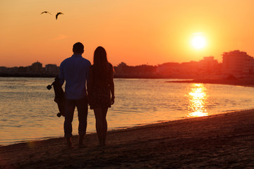 Silhouette of happy couple standing near the sea and take a photo during sunset. Girlfriend and boyfriend during romantic date moment. Love concept of peace or quiet vacation for loving hearts.