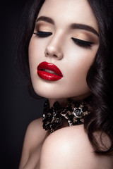 Beautiful woman portrait. Young lady posing close up on black background. Glamour make up, red lipstick. Gorgeous jewelry on neck.