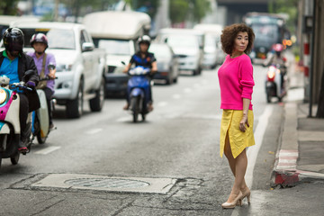 Young asian woman stands near a busy city highway.