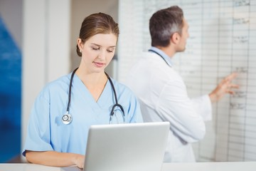 Female doctor working on laptop with colleague pointing at chart in hospital