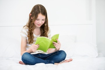 Girl reading book on bed at home