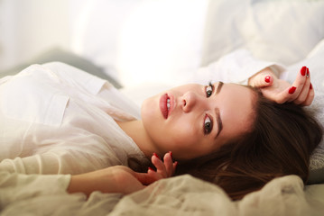 Beautiful thoughtful girl lying in bed on background of sunlight