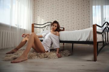Beautiful smiling brunette woman with long slim legs posing bedroom