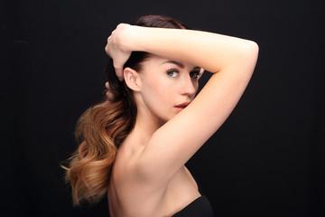 Długie zmysłowe włosy.Portret kobiety z pięknymi długimi włosami na czarnym tle