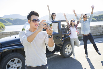 Man taking picture while friends enjoying in background