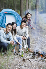 Young friends sitting beside campfire preparing food