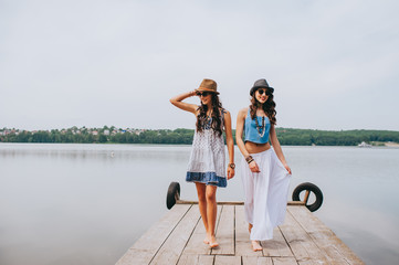 two beautiful girl friends on the dock