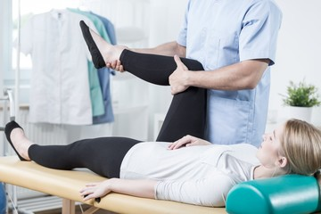 Chiropractor stretching female leg