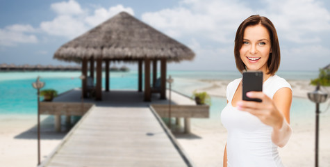 happy woman taking picture by smartphone on beach