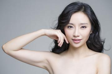 Young beautiful woman touching her face