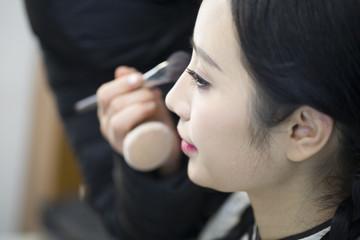 Makeup artist applying make-up to young woman