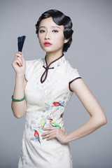 Young beautiful woman in traditional cheongsam with folding fan