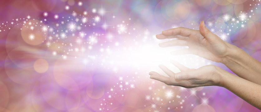 The Magic of Healing - female parallel hands with a burst of white light between and outwardly flowing sparkles on a pink purple background with plenty of copy space
