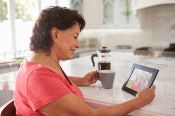 Senior Hispanic Woman At Home Looking At Old Photograph