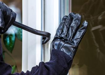 Ein unbekannter Einbrecher hebelt eine Terrassentür auf