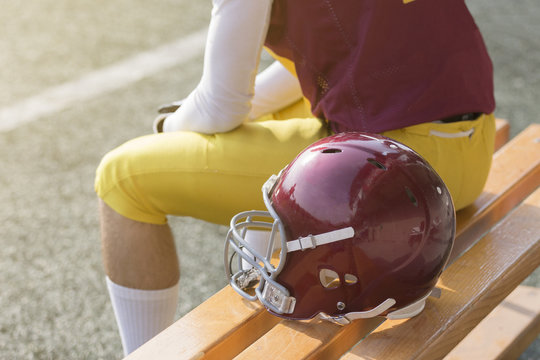 American football player sitting on bench and helmet next to him