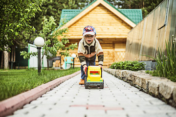 Caucasian boy playing with toy truck in backyard