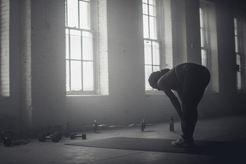 Black woman stretching in dark gym