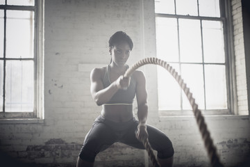 Black woman tossing ropes in dark gym