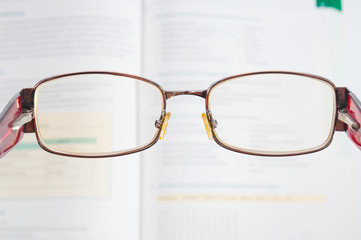 Eyeglasses and blurred textbook