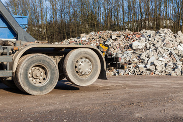 Recycling trucks with rubble in the background