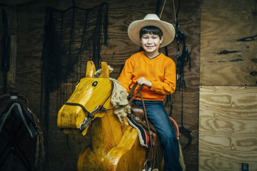Caucasian boy riding toy wooden horse