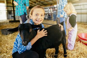 Caucasian girl petting goat in barn