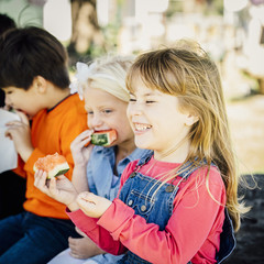 Caucasian children eating watermelon outdoors