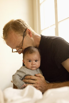 Father kissing baby boy on bed