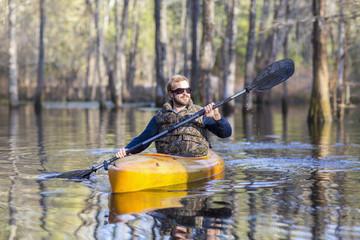 Caucasian man rowing canoe in river