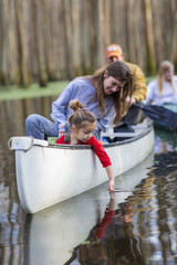 Family sitting together in canoe on river