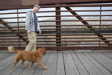 Caucasian man and dog walking on wooden bridge
