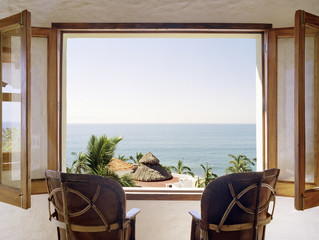 Empty chairs facing open window overlooking ocean