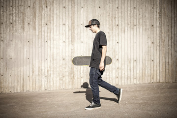 Caucasian man carrying skateboard near wooden wall