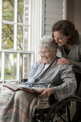 Woman looking at photo album with mother in wheelchair