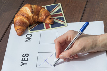 Female hand filled YES in the printed form. On the wooden table is lying a napkin English flag design, on which is symbolically lying a French croissant.
