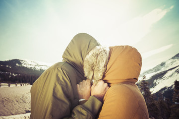 Caucasian couple hugging in parka hoods near mountain