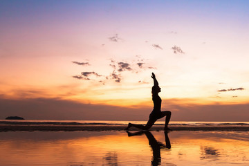 Wall Mural - beautiful yoga exercise on the beach at sunset, background with copyspace
