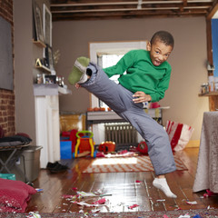 Black boy doing karate kick in living room